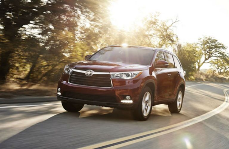 Driver side exterior view of a red 2015 Toyota Highlander