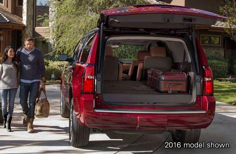 Couple walks towards open trunk of 2016 Chevy Tahoe