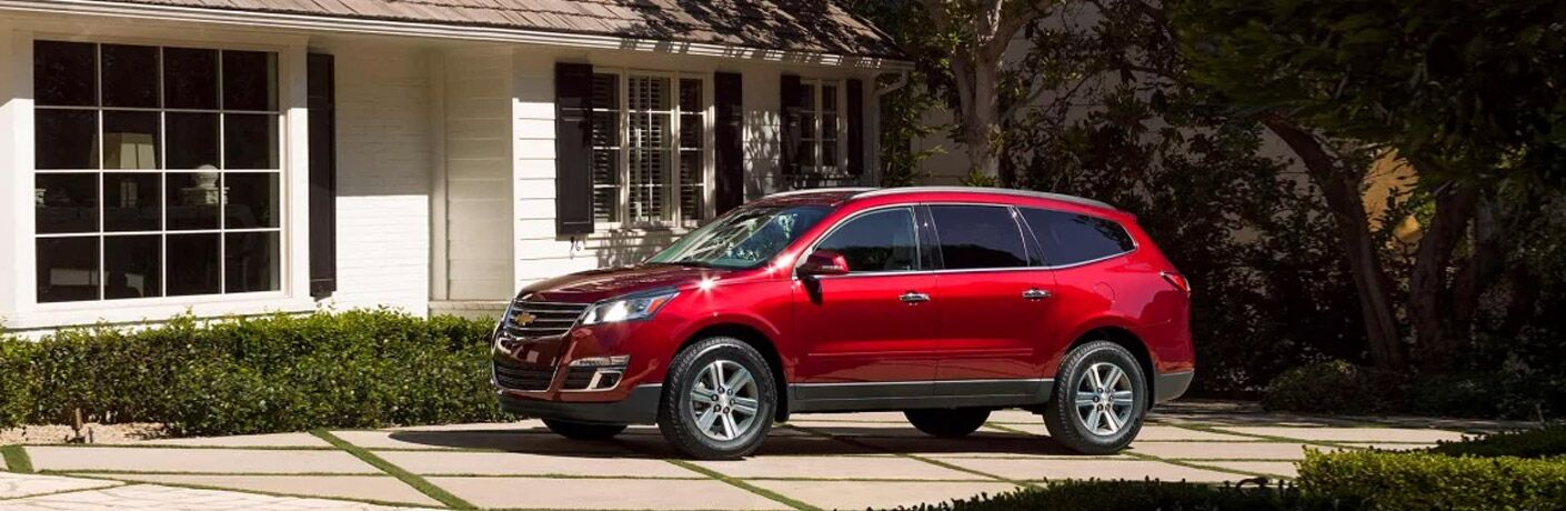Driver side exterior view of a red 2017 Chevy Traverse