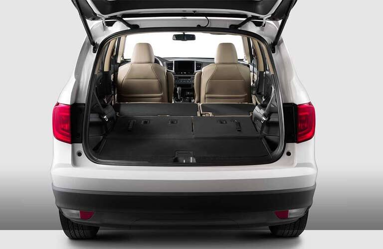 Looking into the cargo area of the 2017 Honda Pilot with the rear seat folded flat for maximum cargo carrying