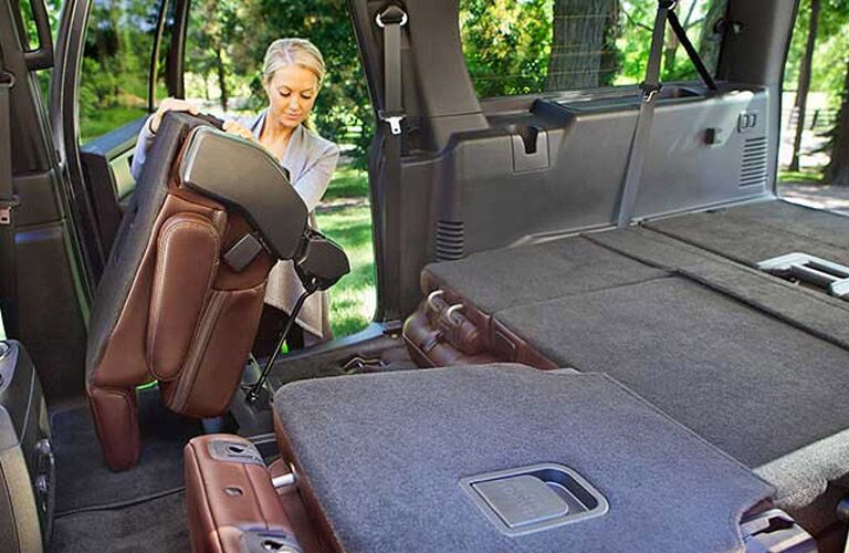 Woman folding the rear seats of the 2017 Ford Expedition flat for storage