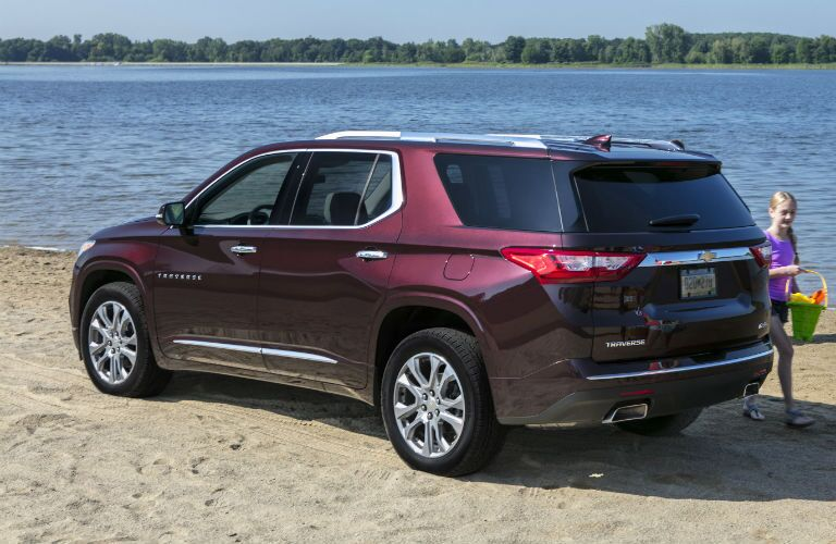 Rear driver side exterior view of a red 2018 Chevy Traverse