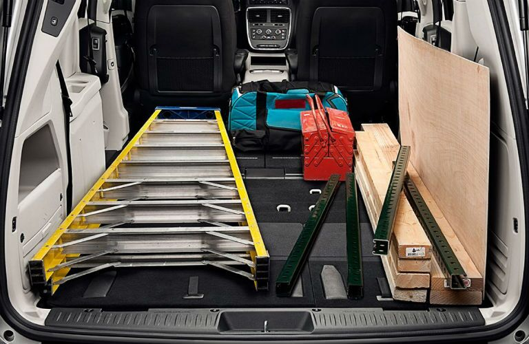 Rear seats folded flat in the 2018 Dodge Grand Caravan in order to accommodate a large ladder and construction equipment