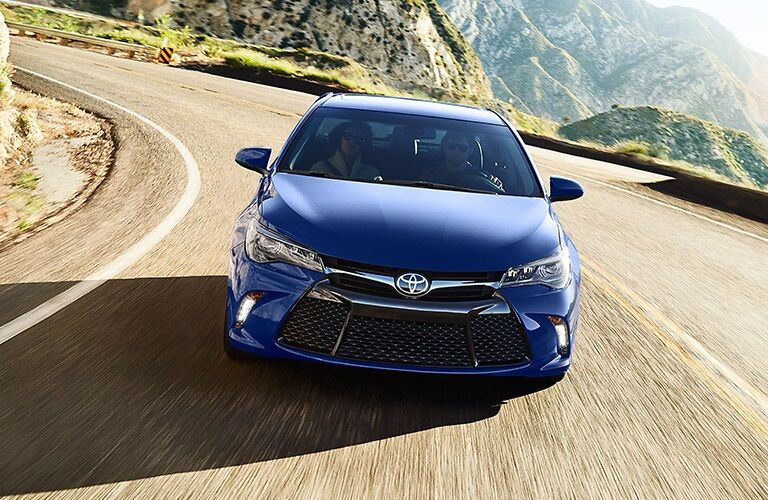 blue 2016 Toyota Camry driving around a corner