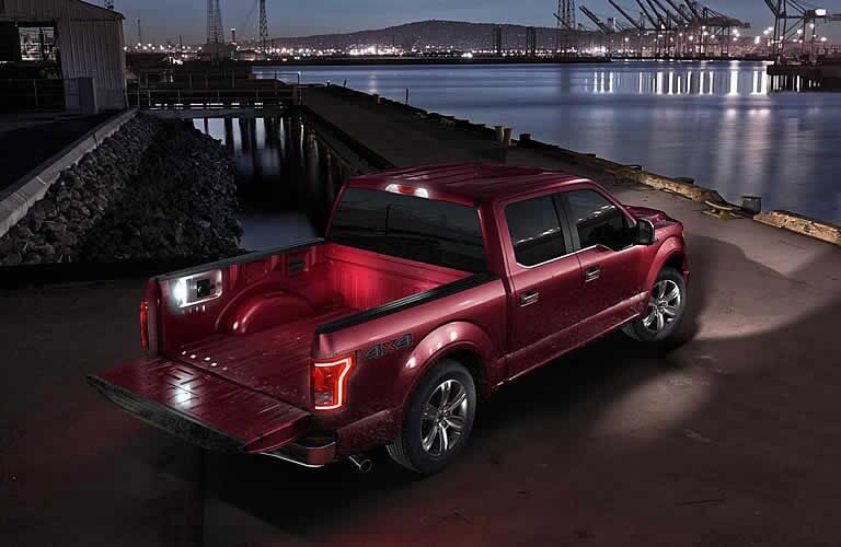 Red Ford F-150 parked near water at night