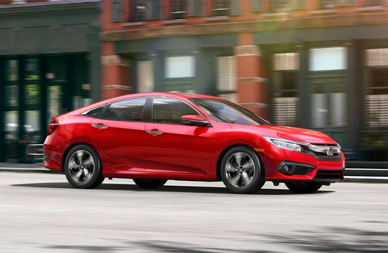 red 2016 Honda Civic driving on city street