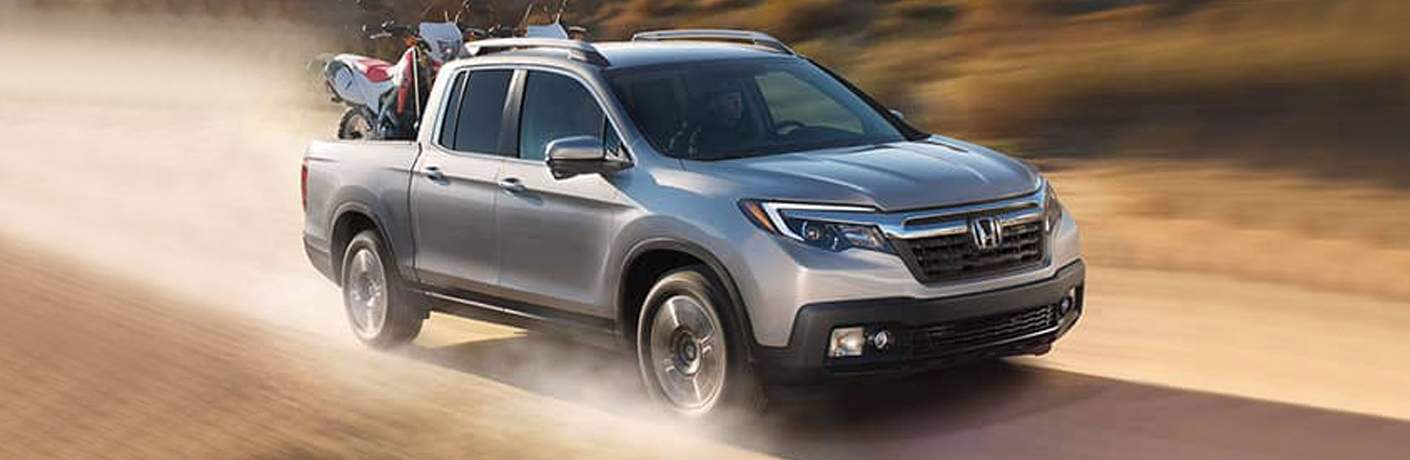 2018 Honda Ridgeline in gray with motorbikes in the truck bed