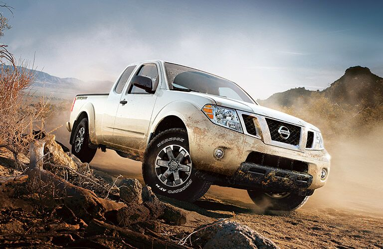 white nissan frontier on rocks and sand