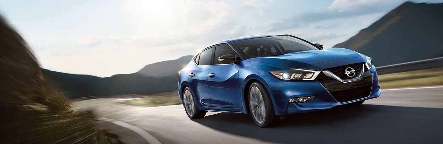 blue nissan maxima driving on road