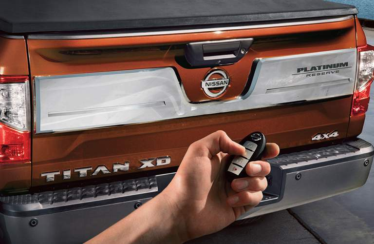 orange nissan titan tailgate with person holding key fob