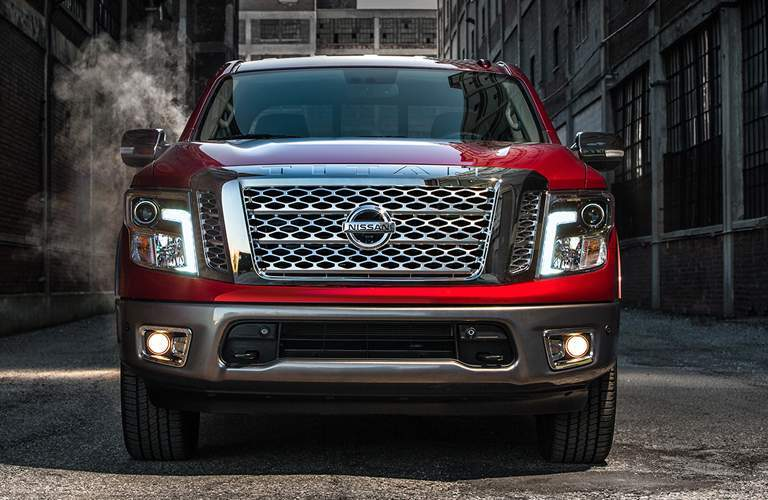 front of red nissan titan '