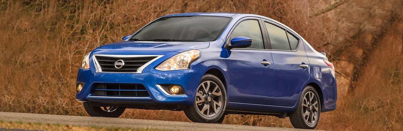 lue nissan versa parked by rocky background