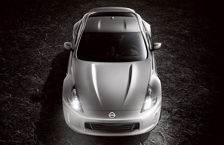 Exterior view of the top of a silver 2019 Nissan 370Z parked in a black showroom