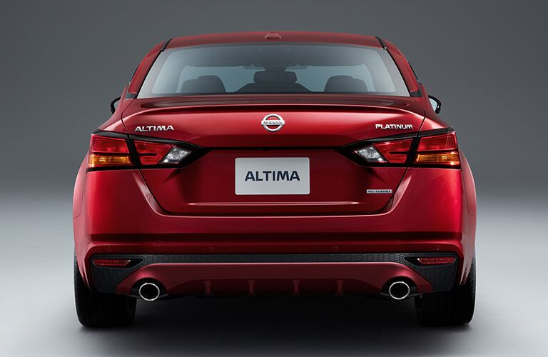 Exterior view of the rear of a red 2019 Nissan Altima parked in a showroom