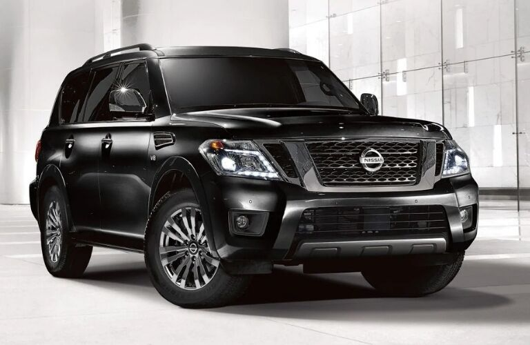 Exterior view of a black 2019 Nissan Armada parked in a white showroom