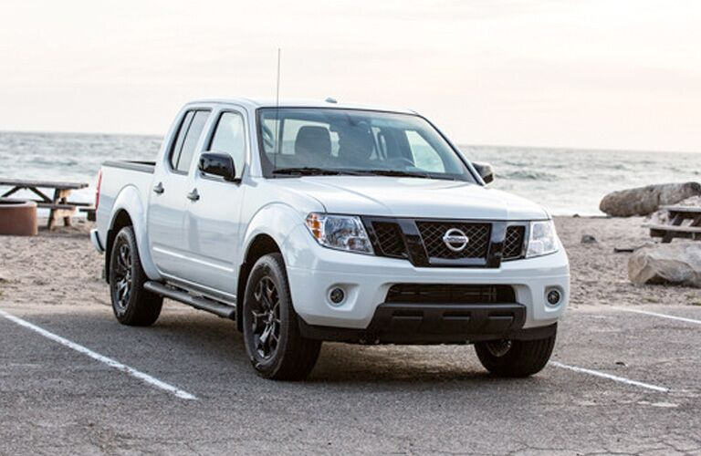 Exterior view of the front of a white 2019 Nissan Frontier parked in a parking lot near the ocean