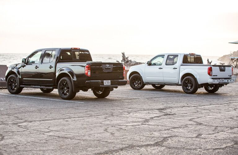 Exterior view of a black 2019 Nissan Frontier and a white 2019 Nissan Frontier parked in a parking lot