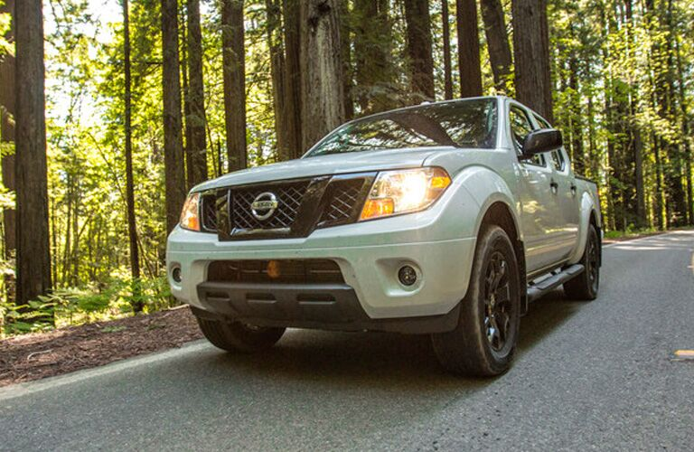 Exterior view of the front of a white 2019 Nissan Frontier driving through the woods