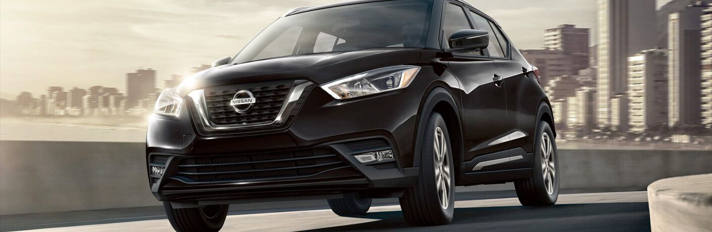 Exterior view of a black 2019 Nissan Kicks driving down the highway