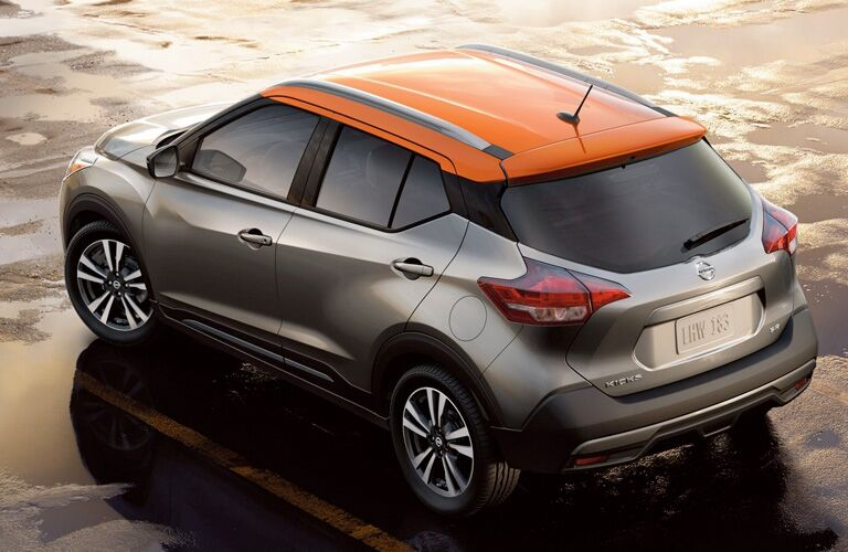 Exterior view of a gray and orange 2019 Nissan Kicks parked in a wet parking lot