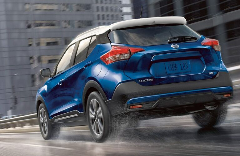 Exterior view of the rear of a blue 2019 Nissan Kicks driving down the highway