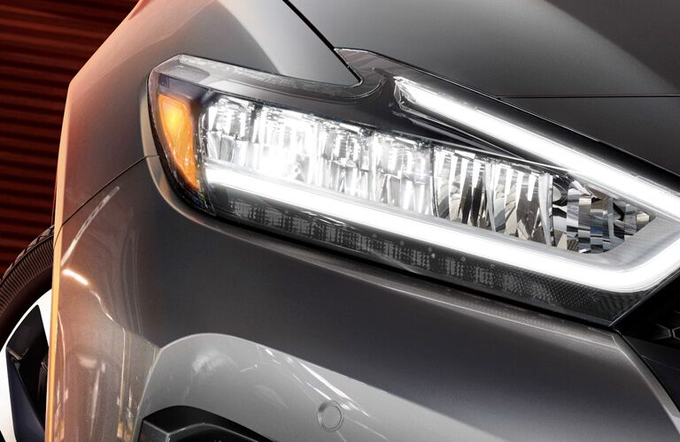 Closeup exterior view of the headlight of a gray 2019 Nissan Maxima