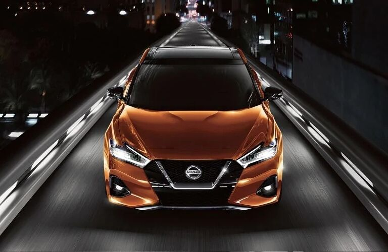 Exterior view of a the front of an orange 2019 Nissan Maxima driving down a single-lane highway
