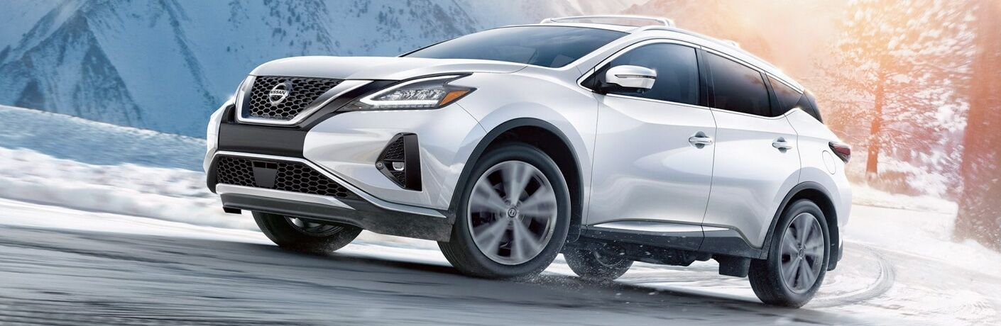 Exterior view of a white 2019 Nissan Murano driving down a snow-covered road in the winter
