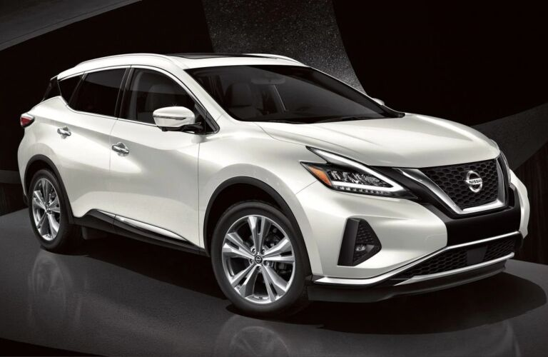 Exterior view of a white 2019 Nissan Murano parked in a black showroom