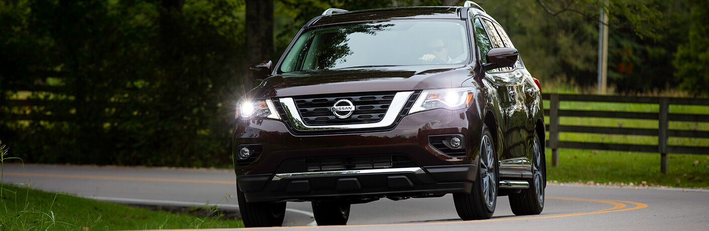 Exterior view of the front of a brown 2019 Nissan Pathfinder driving down a country road