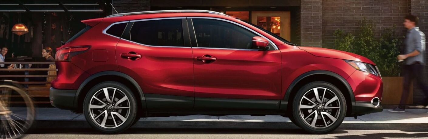 Exterior view of a red 2019 Nissan Rogue Sport parked on a city street