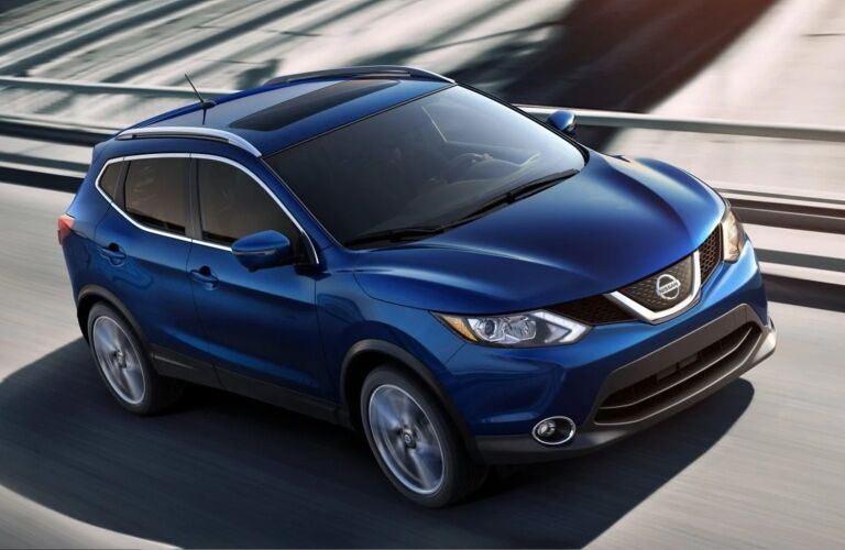 Exterior view of the front of a blue 2019 Nissan Rogue Sport driving down the highway