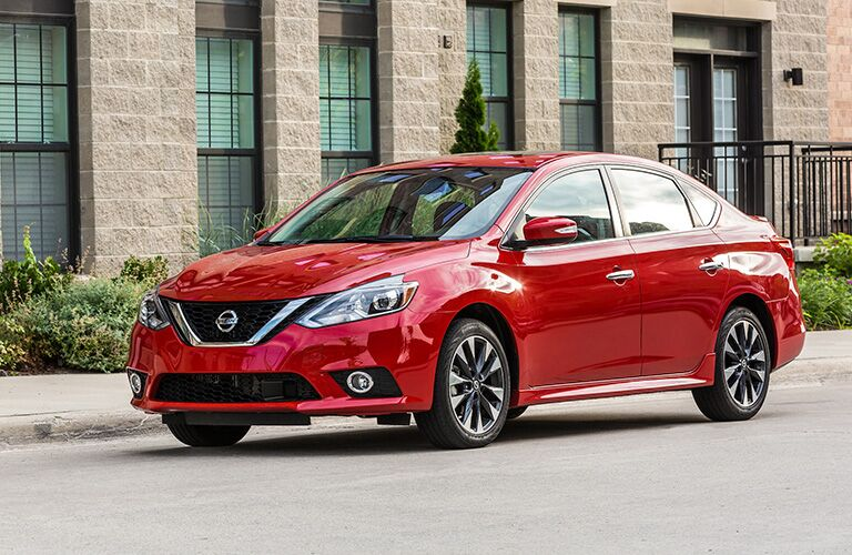 Exterior view of the front of a red 2019 Nissan Sentra parked on a city street