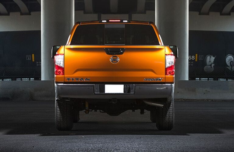 Exterior view of the rear of an orange 2019 Nissan TITAN parked in a parking garage