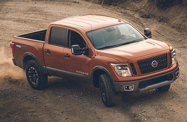 Exterior view of a bronze 2019 Nissan TITAN driving around a dirt job site