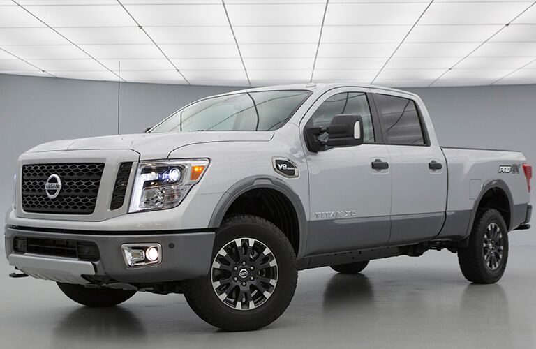 Exterior view of a white 2019 Nissan TITAN parked in a white showroom