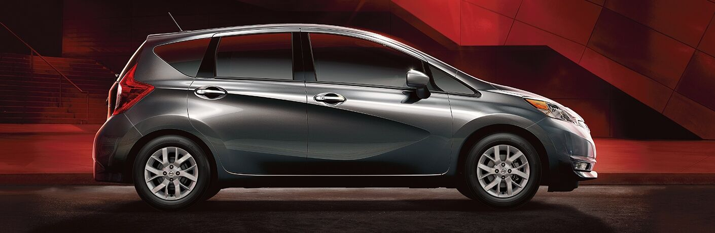 Exterior view of a grey 2019 Nissan Versa Note parked in a black and red showroom