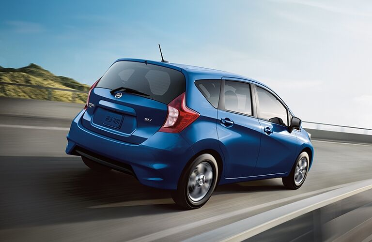 Exterior view of the rear of a blue 2019 Nissan Versa Note driving down the highway