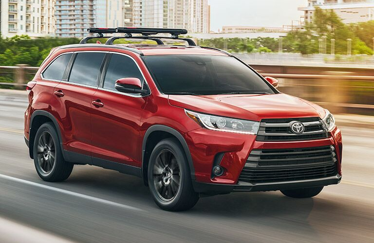 Exterior view of a red 2019 Toyota Highlander driving over a bridge in the city