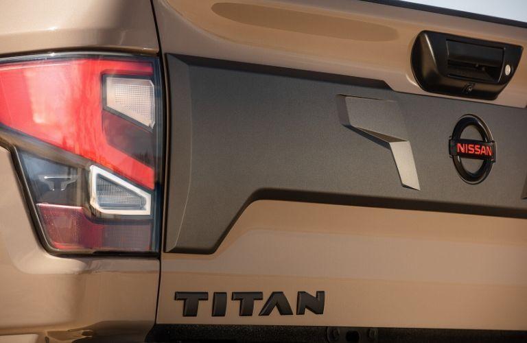 "Closeup exterior view of the rear and ""TITAN"" badge on a tan 2020 Nissan TITAN"