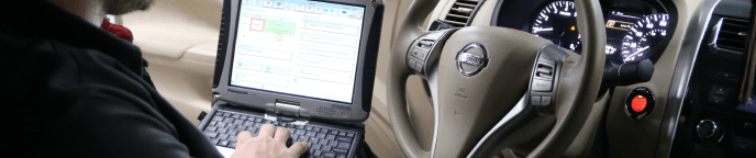 mechanic using laptop in driver's seat of a nissan
