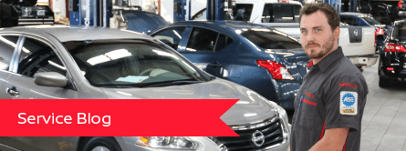 man in auto shop with cars behind him