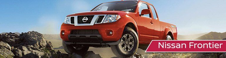 red-orange nissan frontier on top of rocks
