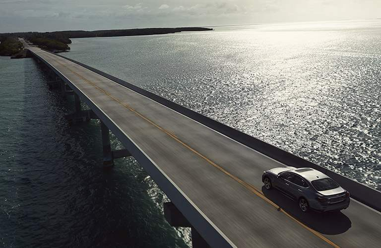 infiniti q70 driving on bridge over water