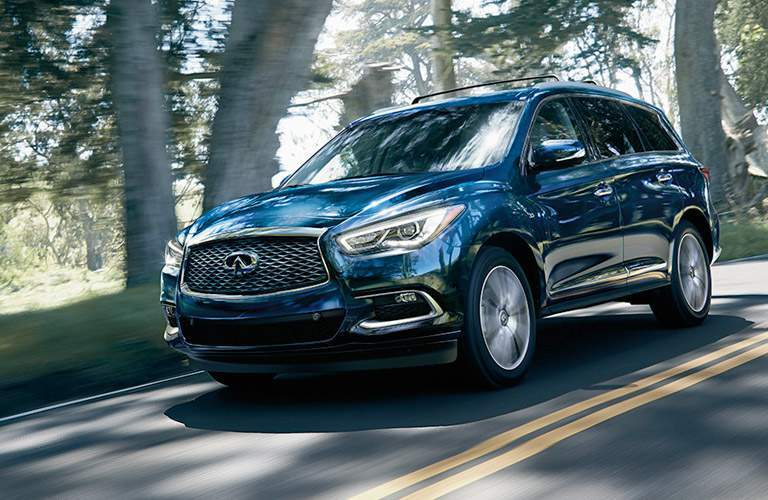 infiniti qx60 driving on road near trees