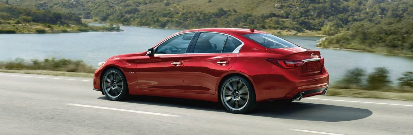 Exterior view of a red 2019 INFINITI Q50 driving down a highway near a lake
