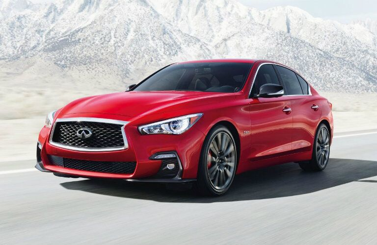Exterior view of the front of a red 2019 INFINITI Q50 driving down a highway in the mountains