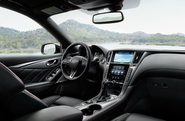 Interior view of the black seating, steering wheel and touchscreen inside a 2019 INFINITI Q50