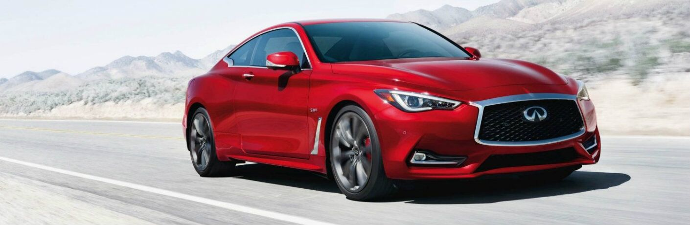 Exterior view of the red 2019 INFINITI Q60 driving down a highway with mountains in the background
