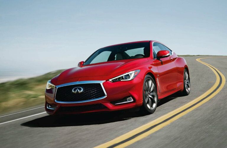 Exterior view of the front of a red 2019 INFINITI Q60 driving down a winding road